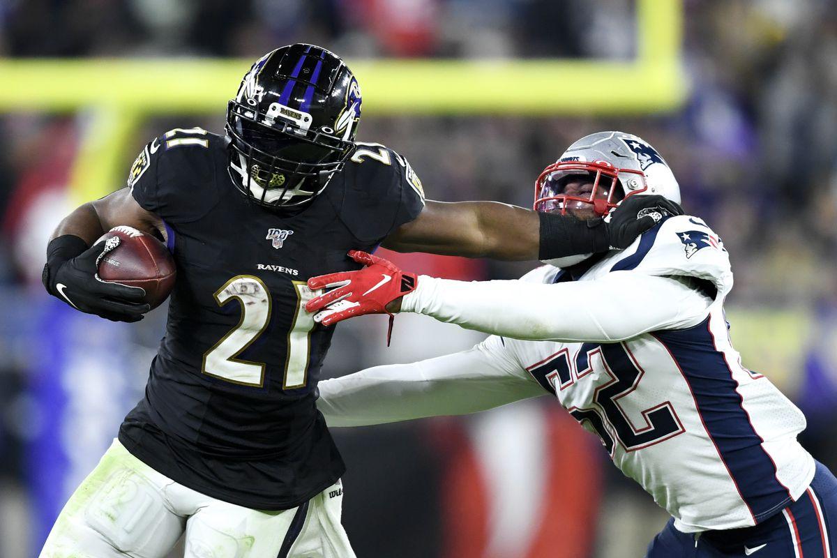Baltimore Ravens running back Mark Ingram runs the ball as New England Patriots outside linebacker Elandon Roberts defends during the fourth quarter at M&T Bank Stadium.