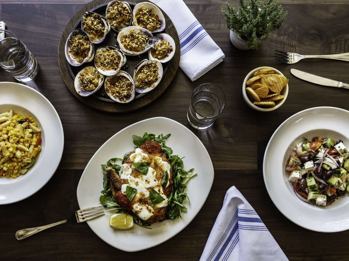 A spread of dishes including pastas, salad, and stuffed clams are laid out on white dishes set on a dark wooden table with blue and white-striped napkins laid in between and silverware scattered around.