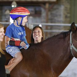 William Buttars, 5, rides Ziggy while his mom, left, and Valerie Duffin walk alongside them Thursday at the Buffalo Ranch in Farmington as part of a therapeutic riding program organized by the nonprofit group Therapeutic Assets.