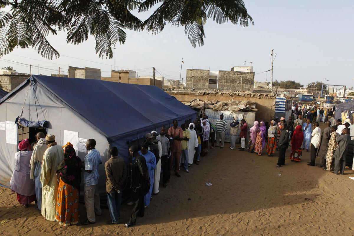 Voters wait in line to cast their votes outside tents erected to serve as polling stations, in the Guediawaye neighborhood of Dakar, Senegal Sunday, March 25, 2012.