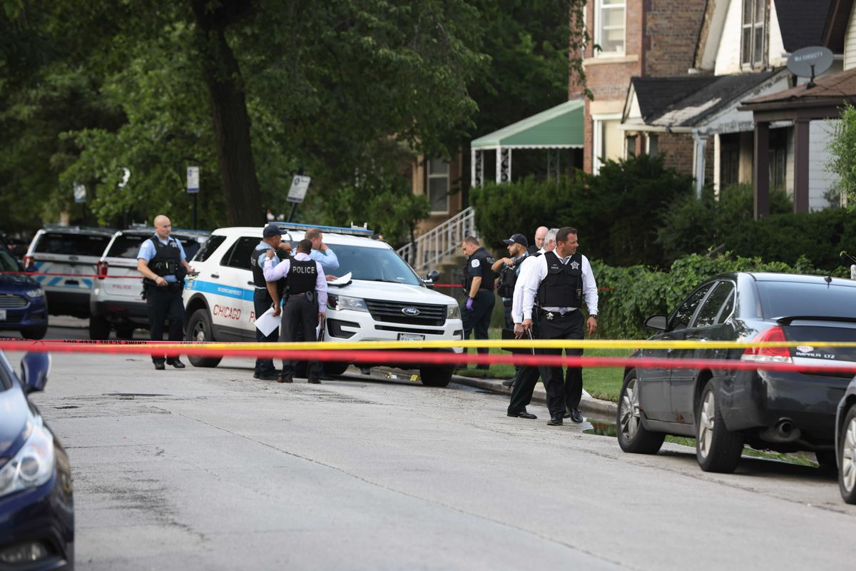 Police investigate the scene where a 25-year-old man was fatally shot July 13, 2021, in the 7000 block of South Normal Avenue.