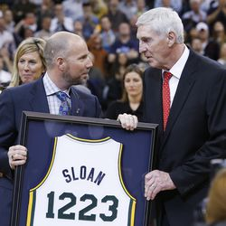 Steve Miller hands former Utah Jazz coach Jerry Sloan a jersey as Sloan's banner is unveiled in his honor during halftime of the Utah Jazz game in Salt Lake City Friday, Jan. 31, 2014.