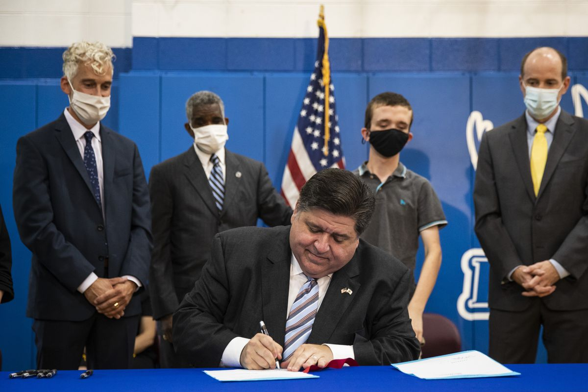 Gov. J.B. Pritzker signs two pieces of legislation into law — aiming to help students with disabilities — during a news conference Wednesday at Southside Occupational Academy High School.