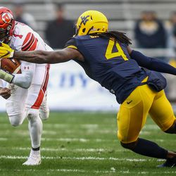Utah Utes quarterback Tyler Huntley (1) runs through the tackle of West Virginia Mountaineers cornerback Mike Daniels Jr. (4) at the Zaxby's Heart of Dallas Bowl between the Utah Utes and the West Virginia Mountaineers in Dallas Texas on Tuesday, Dec. 26, 2017.