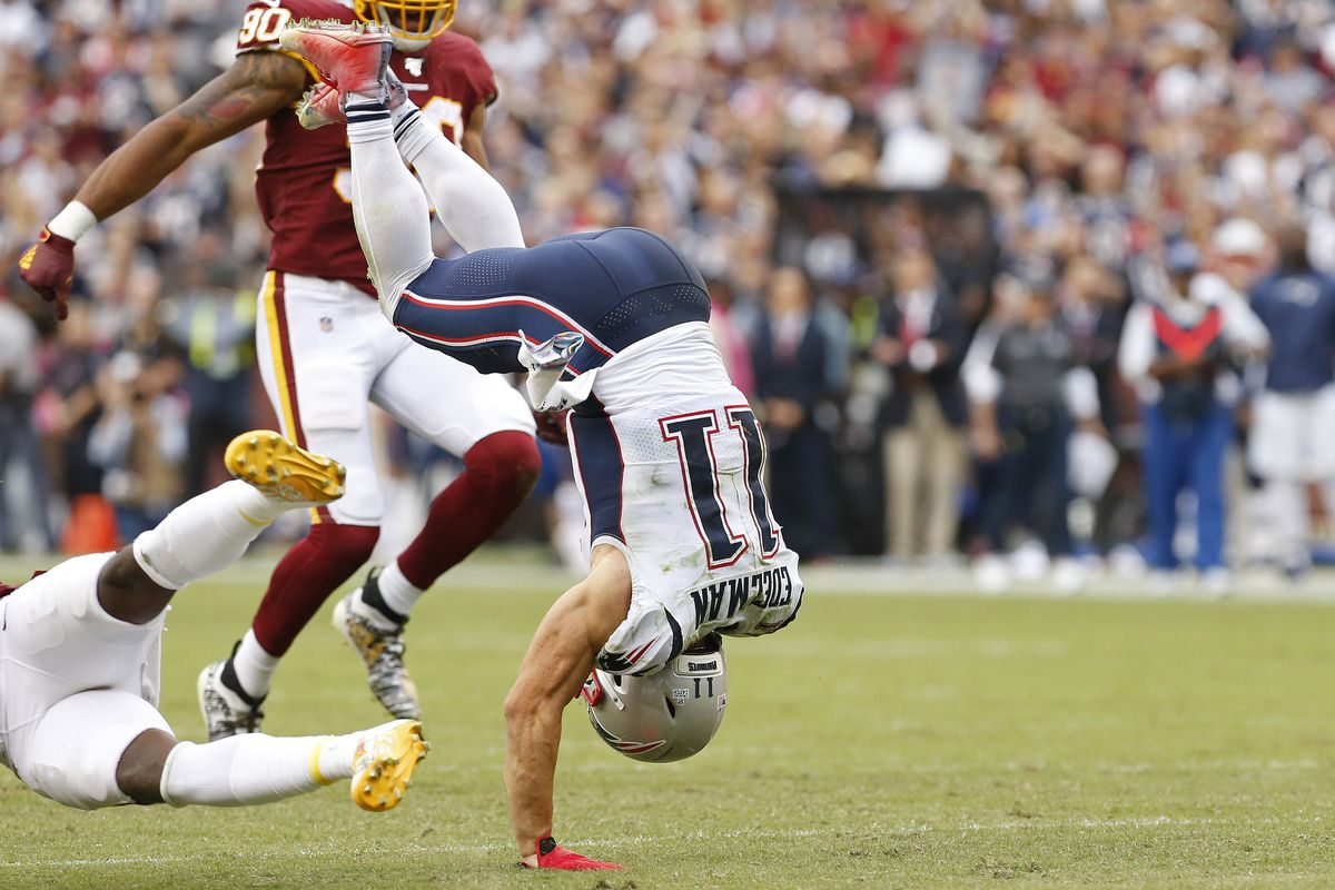 New England Patriots wide receiver Julian Edelman flips while carrying the ball after being hit by Washington strong safety Landon Collins in the third quarter at FedExField.