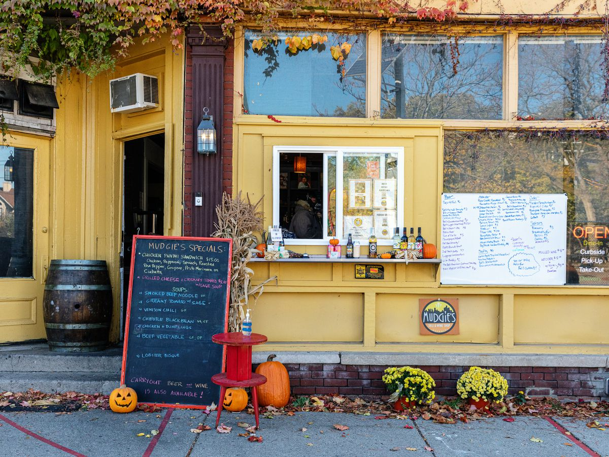 Mudgie's Deliv is shown with fall decorations and a walk-up window with sandwich boards and handwritten menus on either side.