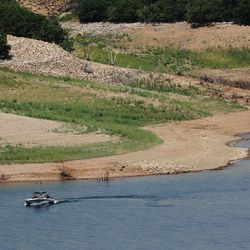 A sailor enjoys the water at Jordanelle State Park on Friday, July 16, 2021.  The water level is low due to drought.