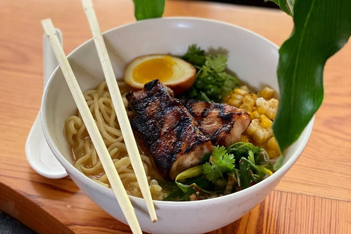 A white bowl of ramen garnished with meat, vegetables, and green leaves