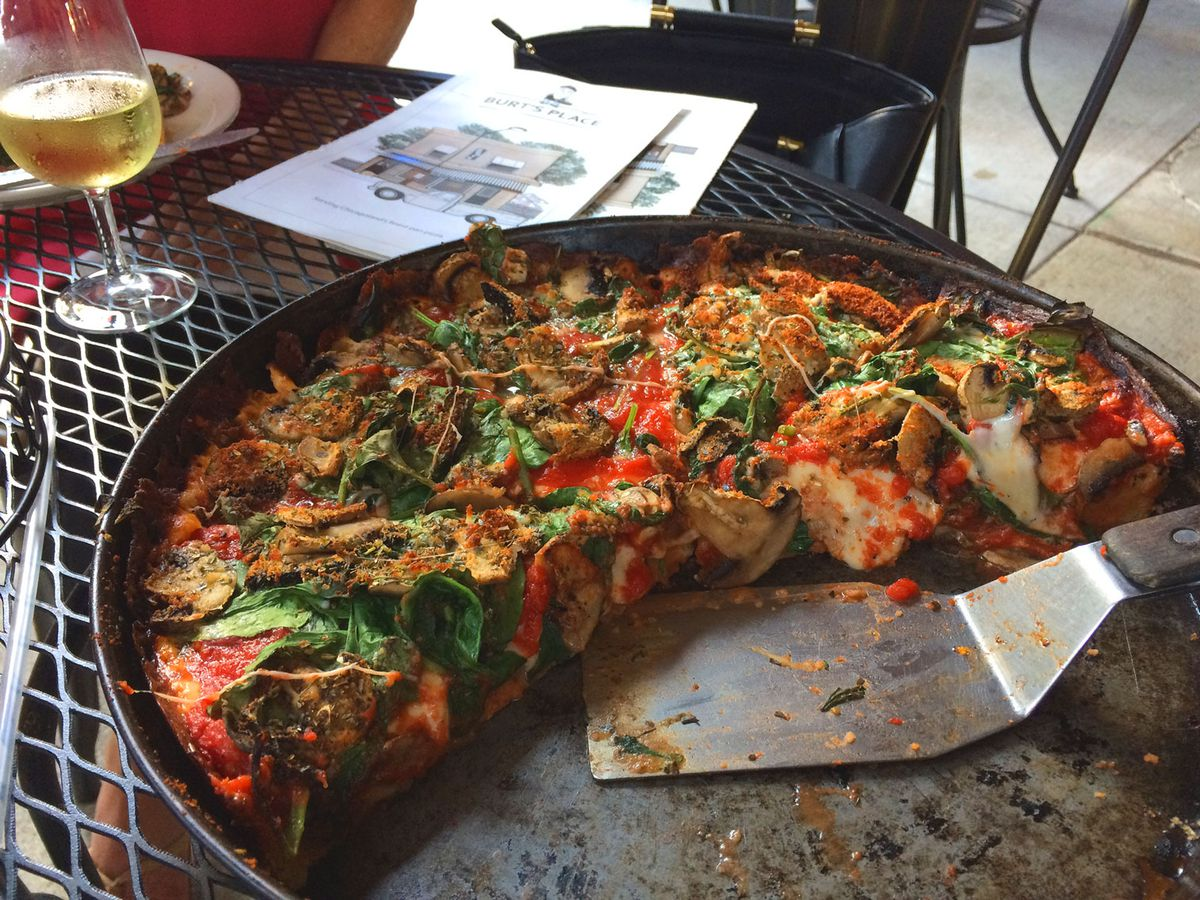 A half portion of pizza in a pan sitting on a patio table.