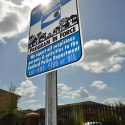 FILE - In this March 23, 2012 file photo, a Neighborhood Watch warning sign is posted outside The Retreat at Twin Lakes gate in Sanford, Fla. The Retreat at Twin Lakes is where 17-year-old Trayvon Martin was shot and killed by neighborhood watch captain George Zimmerman on Feb. 26, 2012. If Martin's family sues over his death, they might not target George Zimmerman but the homeowners association of the neighborhood where the shooting happened and Zimmerman lived.