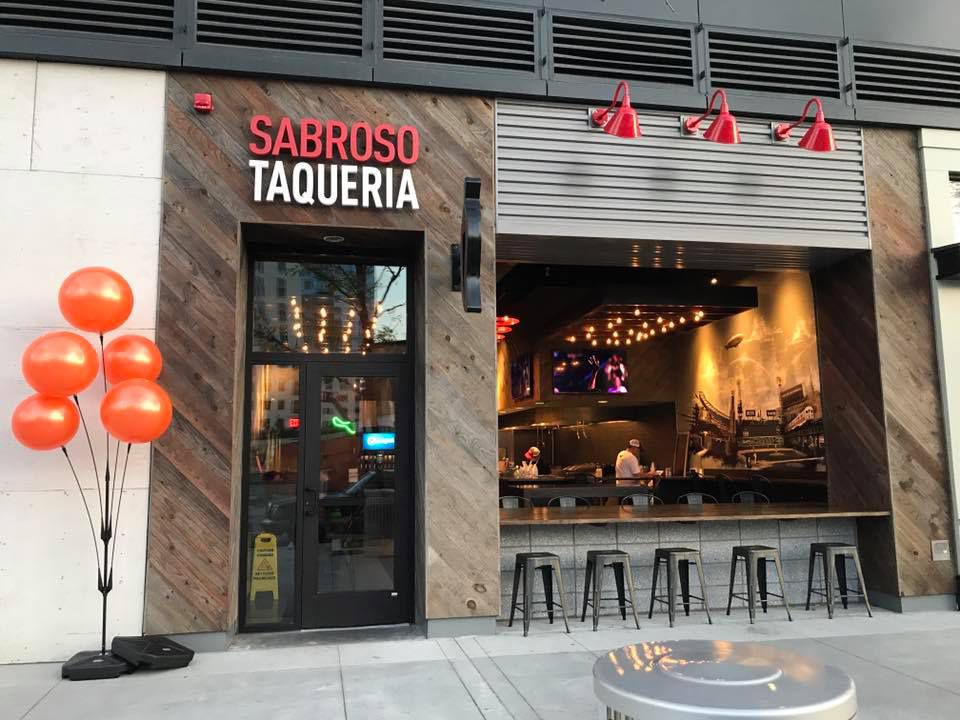 """The exterior of a restaurant features a wide-open front window. Signage reads """"Sabroso Taqueria,"""" and there are orange balloons near the door."""
