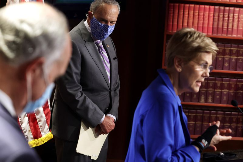 Elizabeth Warren speaking at a podium with Chuck Schumer looking at her.