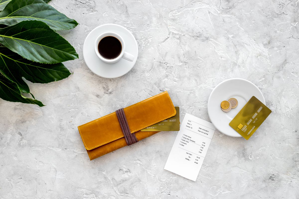A wallet, credit card, coffee cup, and bill arranged on a white table with a green plant off to the side