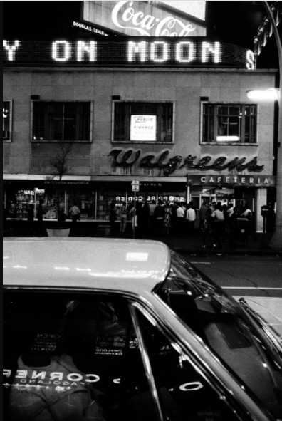 People stand outside a Walgreens to read the electronic news ticker announcing the moon landing on July 20, 1969.