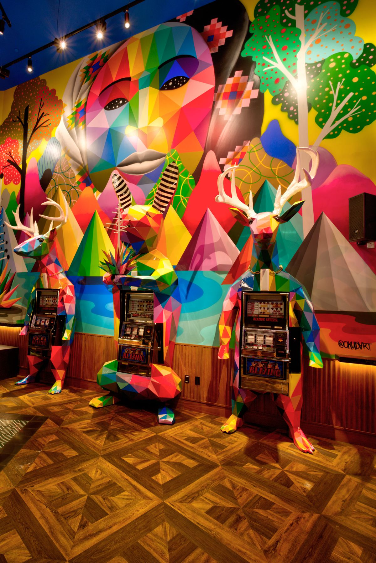 A colorful mural overlooks three slot machines designed like two deer and a rabbit