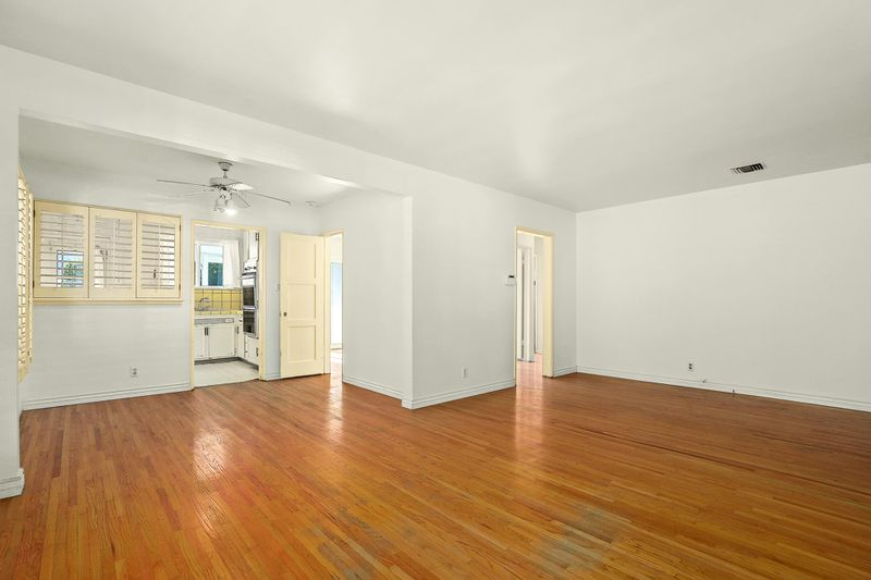 A large open room with hardwood floors. The kitchen is visible just beyond the end of the hardwood.