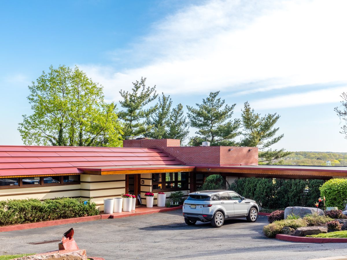 The Crimson Beech by Frank Lloyd Wright. The roof is red and the facade is ivory. The house is one level. There is a parking lot in front of the house.