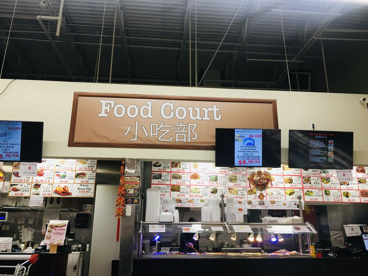 The food court at 168 Asian Mart has side-by-side counters serving Chinese barbecue and noodle dishes with flat screens advertising grocery items on special.