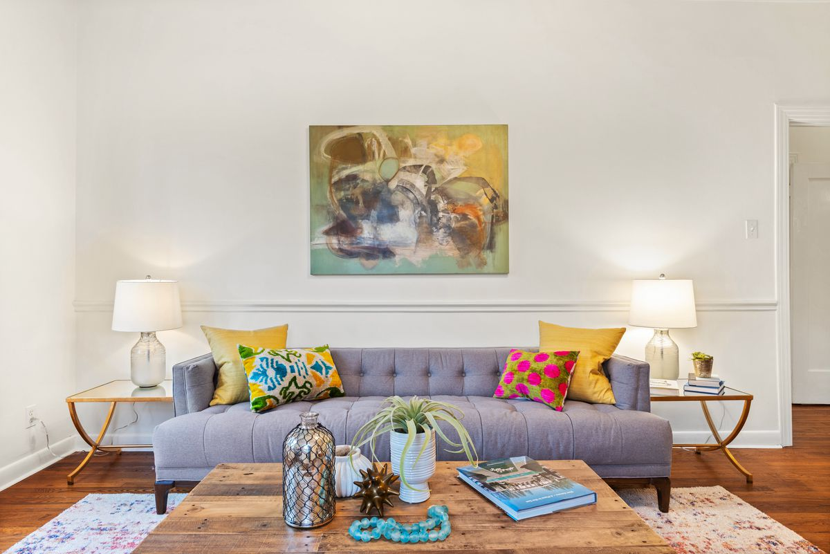 A room with wood floors. There's a chair rail and a painting on the back wall. A couch and matching glass side tables with lamps face a square wood coffee table on a rug.