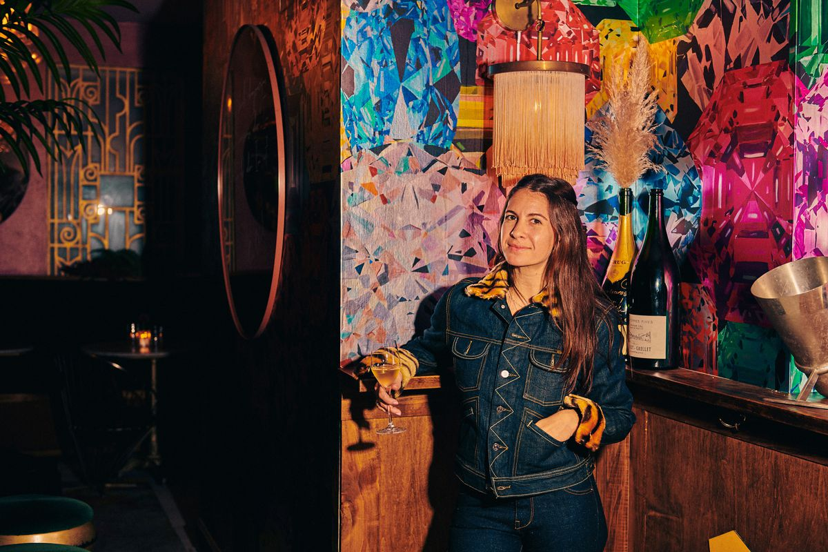Owner Ariel Arce, clad in all blue denim, holds a glass of Champagne at Air's
