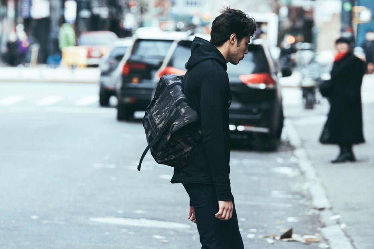 man crossing street with messenger bag