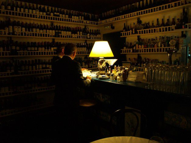 Two servers stand at a bar in a darkened room beside a bright lamp. The walls are lined with wine bottles but are difficult to make out.