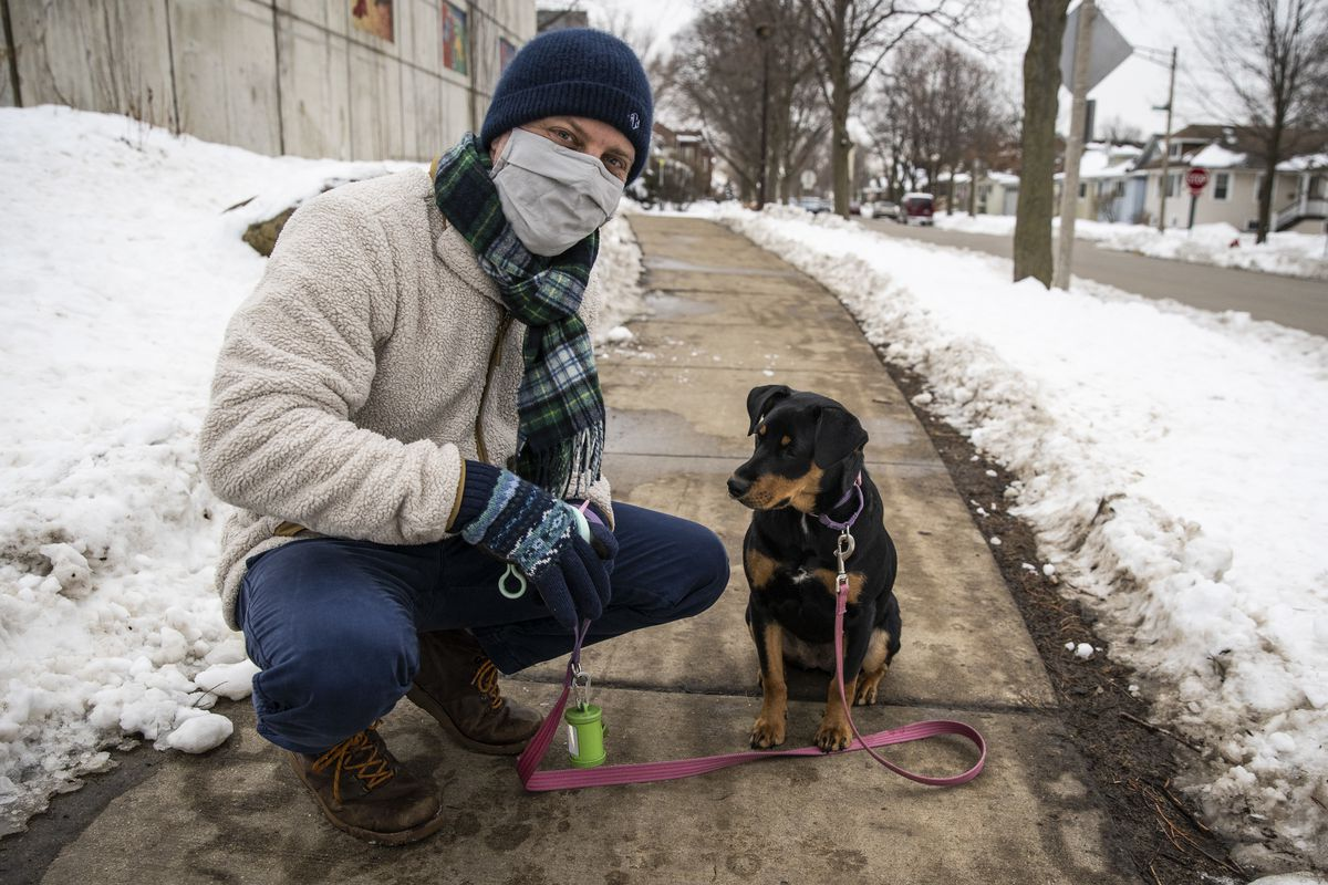 Jeremy Gordon, 41, stops to give treats to his family's puppy Rosie, a 9-month-old shepherd mix, on a walk Thursday near his home in west suburban Oak Park.
