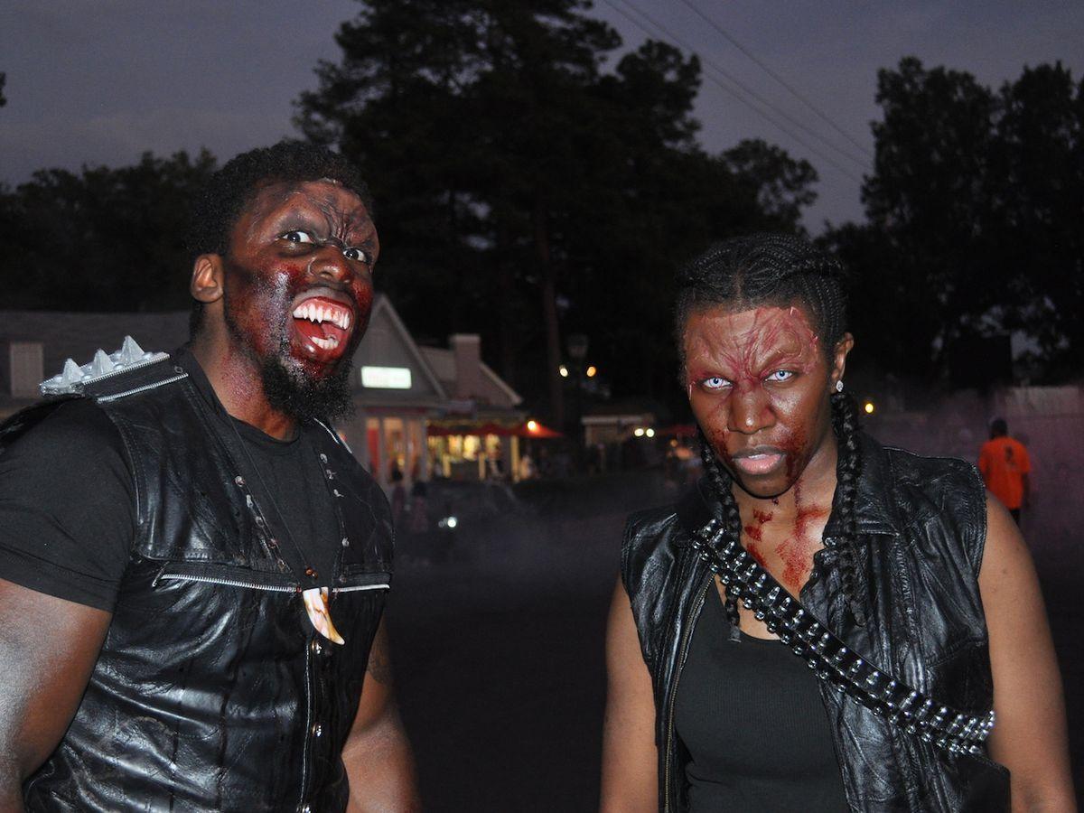 Two men wearing Halloween makeup to look like vampires.