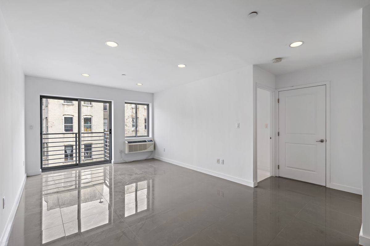 A living area with tiled floors, white walls, and a glass door that leads to a balcony.