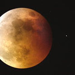A star glows beside eclipsed moon in 2003. Stars are seldom visible near a non-eclipsed moon. Next total eclipse is Wednesday.