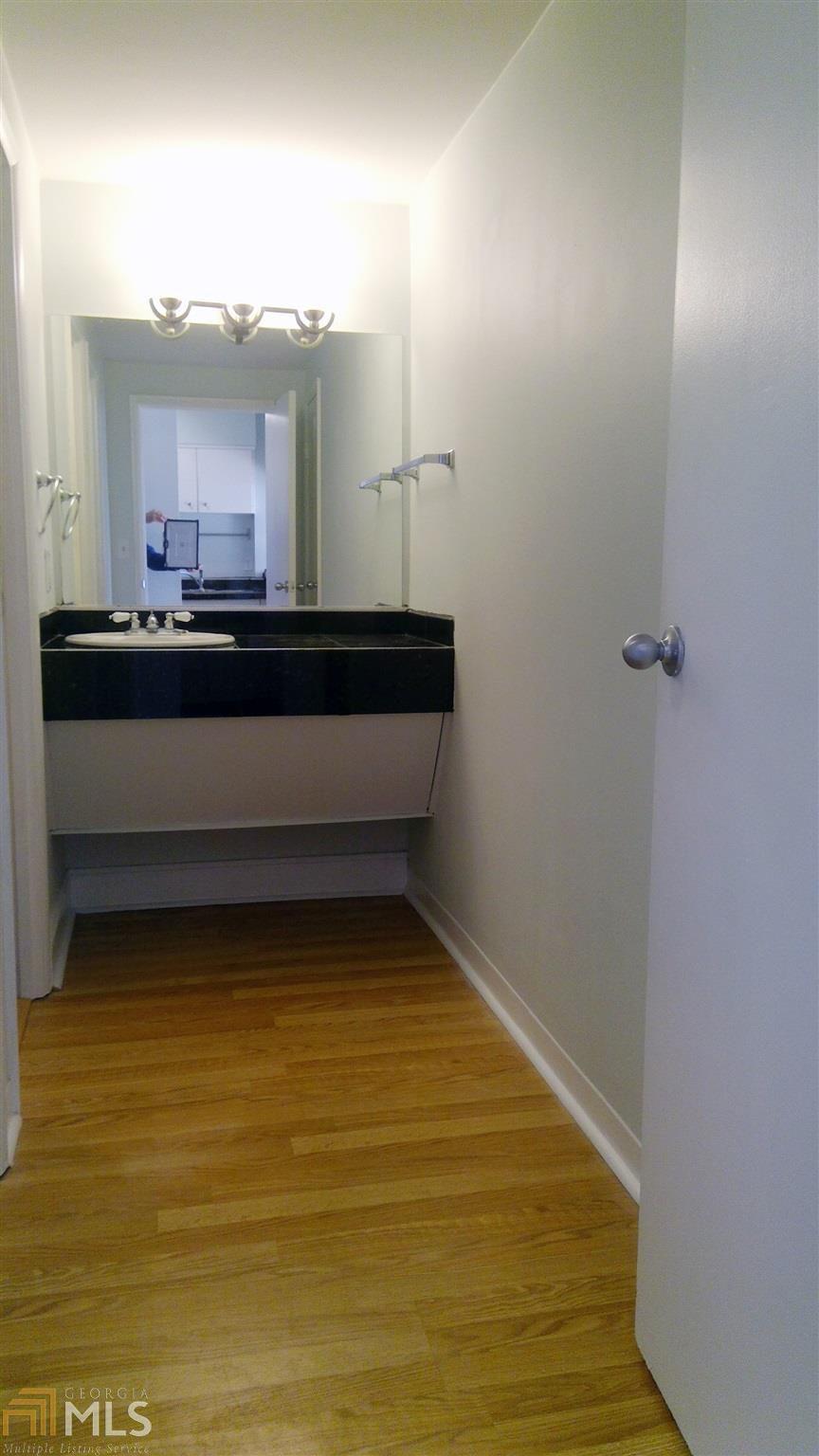 A white bathroom with wood floors.