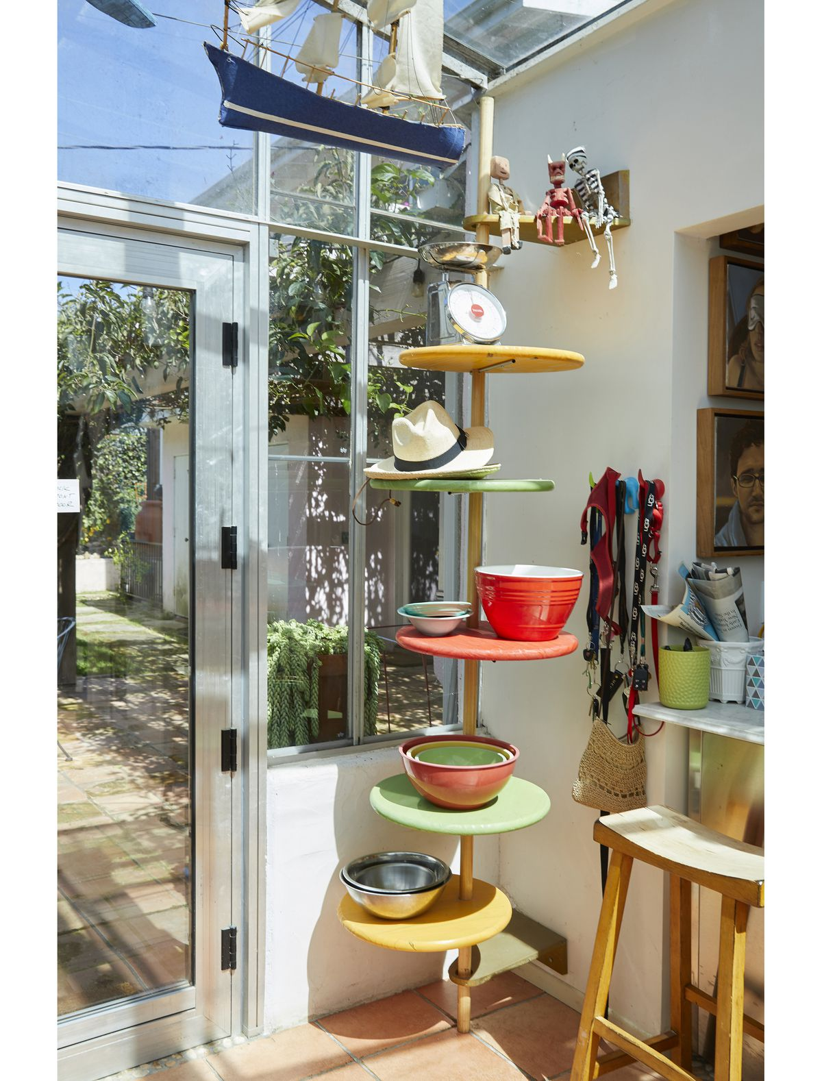 The corner of a room with a long pole that has many shelves. On the shelves are colorful bowls.