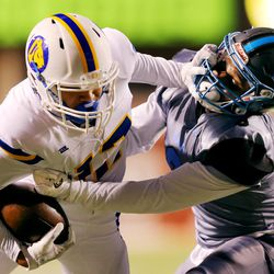 Orem's Puka Nacua is tackled by Sky View's Caleb Christensen as they play in 4A semifinal football action at Rice Eccles stadium at the University of Utah on Friday, Nov. 10, 2017. Orem won 28-12.
