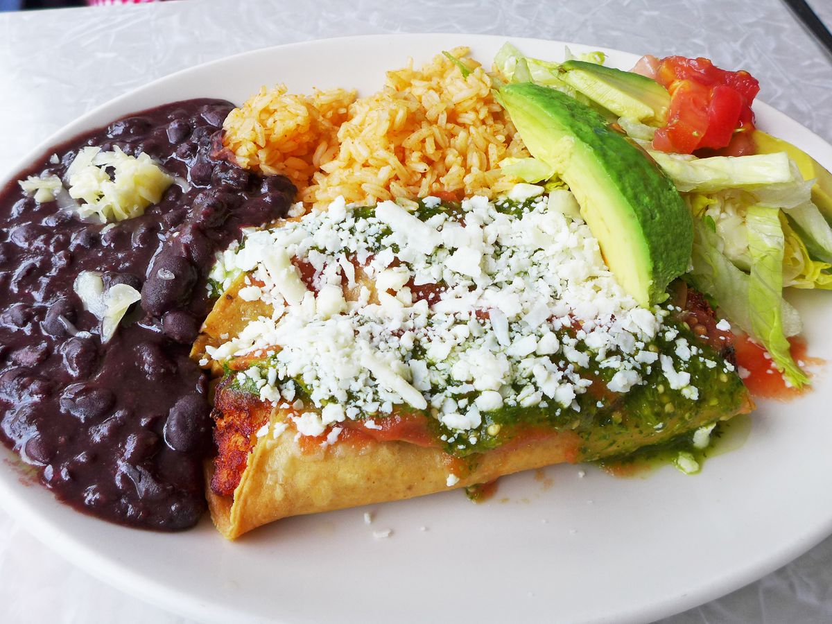 Potato stuffed taquitos snowed with cheese and sided with salad, yellow rice, and black beans.