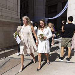 A Newlywed couple walks out after getting married outside the Wrigley Building on N Michigan Ave during the Meet Me on The Mile Sunday Spectacle Sunday, Sept. 26, 2021. 50 couples were married outside the Wrigley Building during The Mile Sunday Spectacle. | Anthony Vazquez/Sun-Times