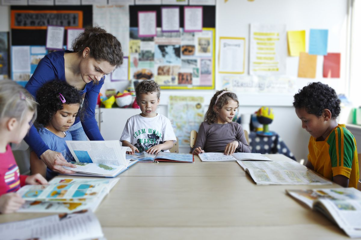 A teacher with young students in the classroom.