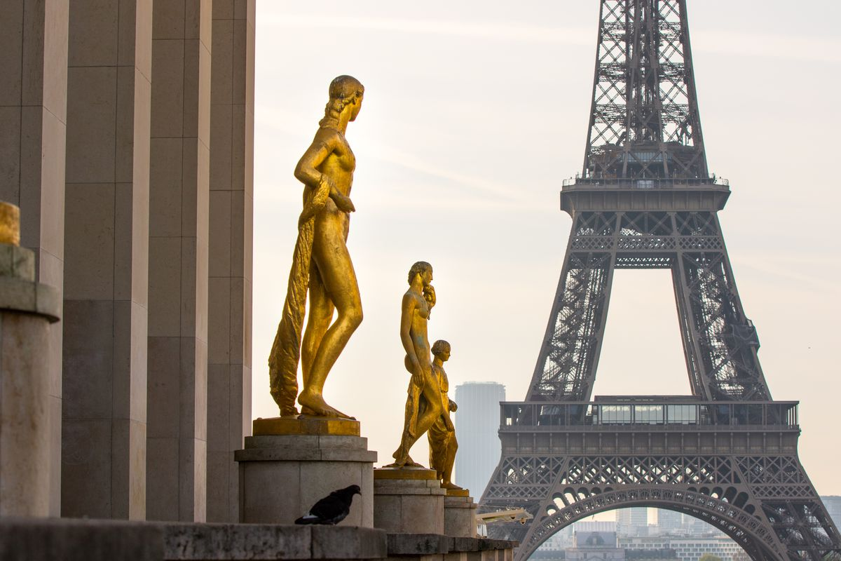 In the foreground are gold statues in the Place du Trocadéro. In the background is the Eiffel Tower in Paris.