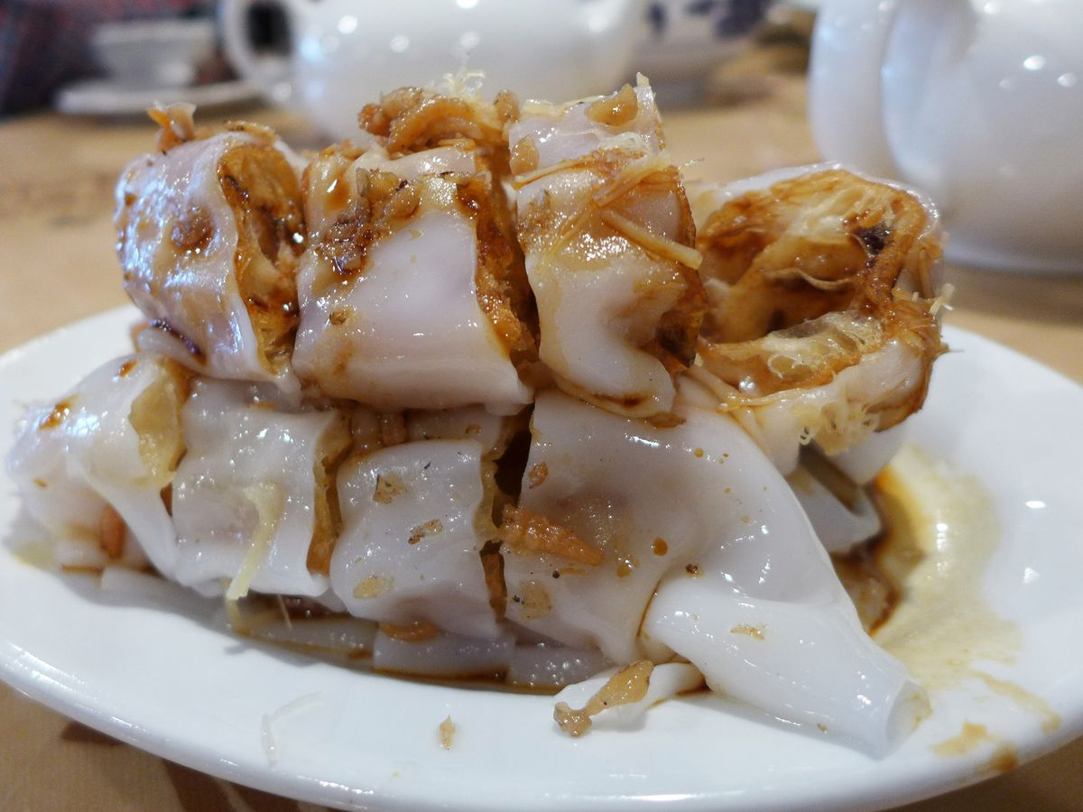 Steamed rice rolls stuffed with fried dough, dried shrimp, and dried scallop on a white plate.