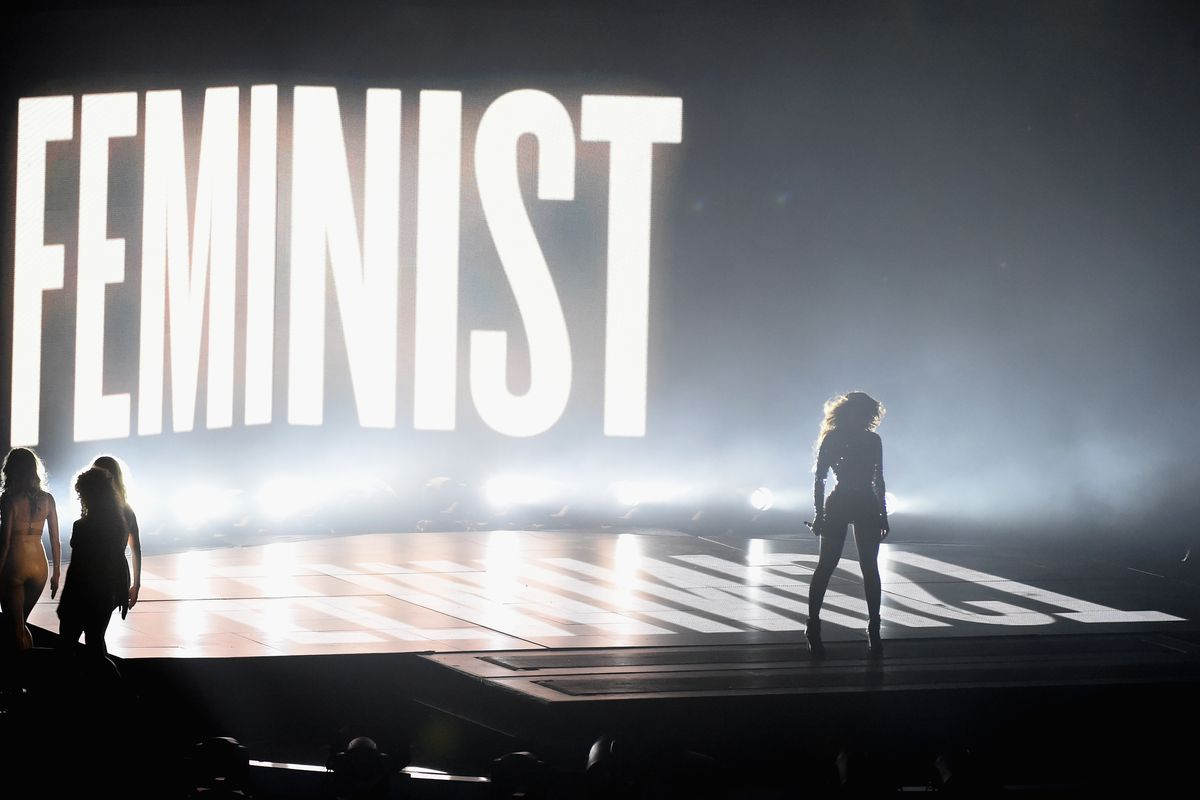 Beyoncé in front of a sign that says FEMINIST