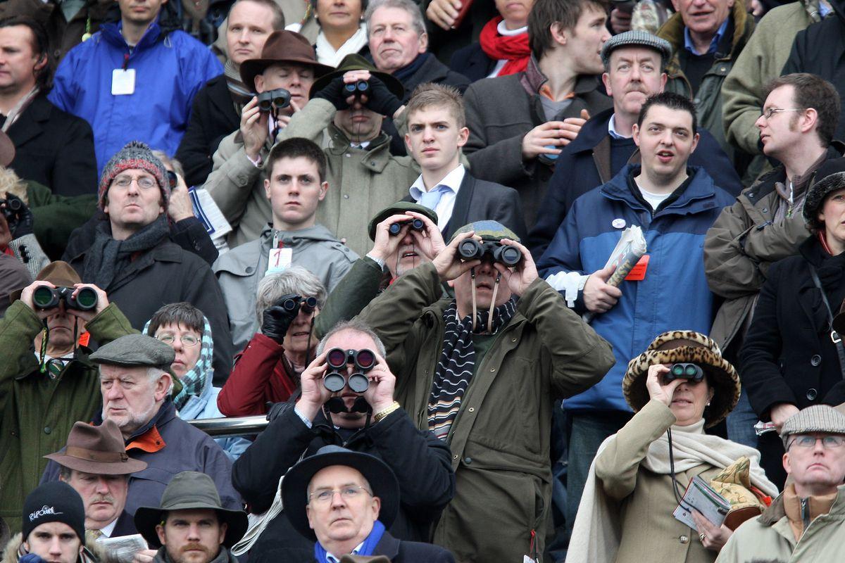 Race-goers look through their binoculars during the Ryanair Chase on day three of the Cheltenham festival at Cheltenham Racecourse