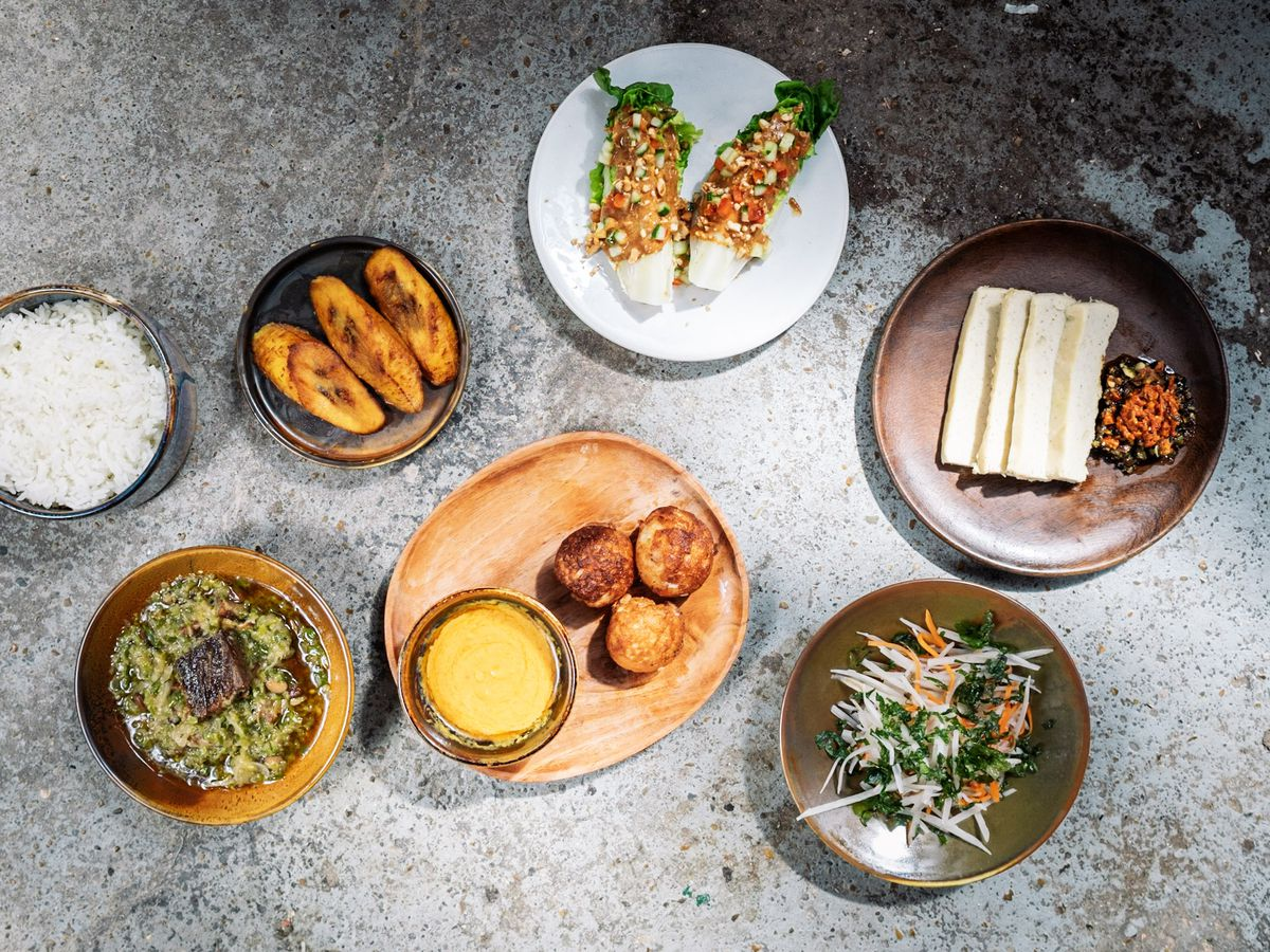 A spread of Nigerian dishes shot from above, including fried plantain; goat amayase; and egusi