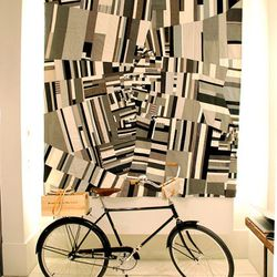 A Bowery Bicycle chills in front of a handmade quilt