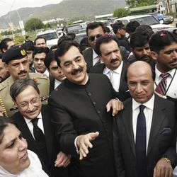 Pakistani Prime Minister Yousuf Raza Gilani, center, makes his way to the Supreme Court for a hearing in Islamabad, Pakistan, Thursday, April 26, 2012.  The Supreme Court convicted Gilani of contempt on Thursday for refusing to reopen an old corruption case against President Asif Ali Zardari on Thursday, but spared him a prison term in a case that has stoked political tensions in the country.(AP Photo/B.K. Bangash)