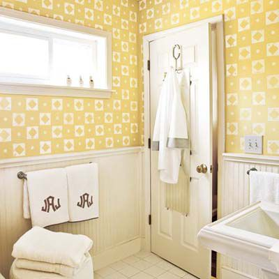 Yellow bathroom with white wainscoting and yellow walls with decorative design.