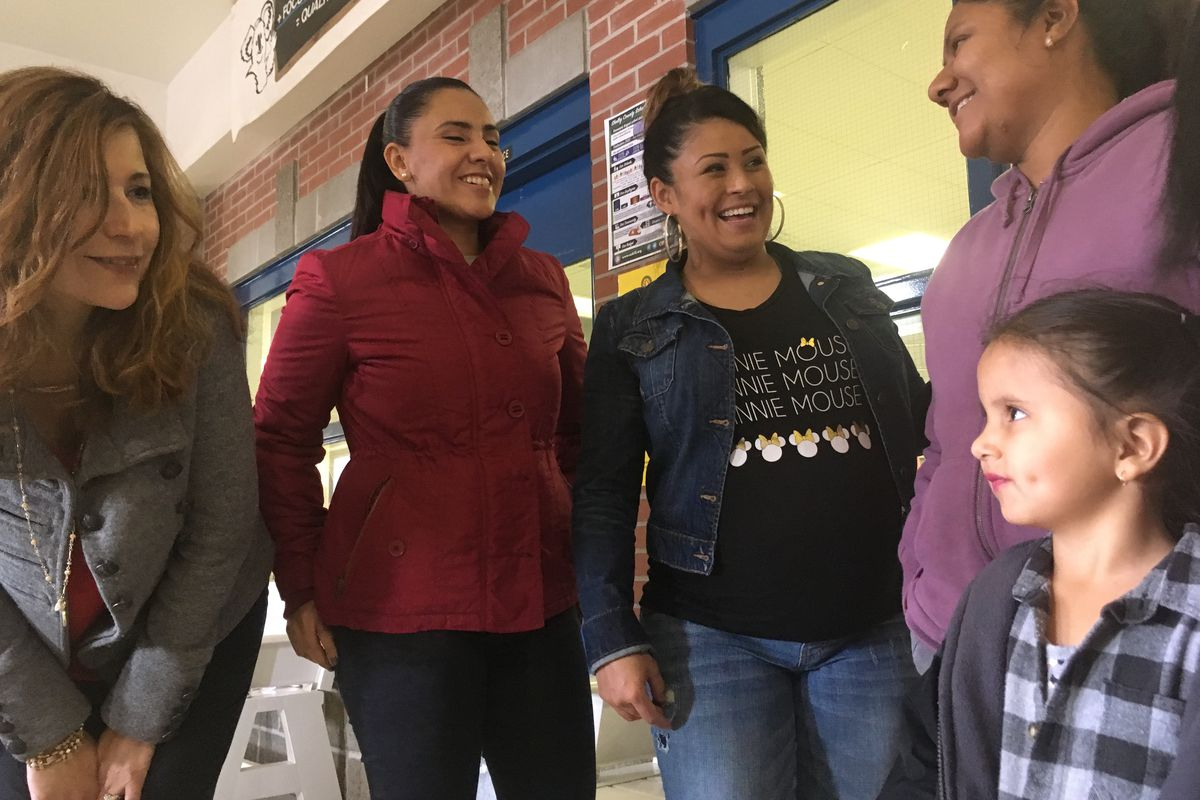 Kate Bond Elementary School's bilingual mentor Lissette Bailey, left, talks with parents after a recent English class.