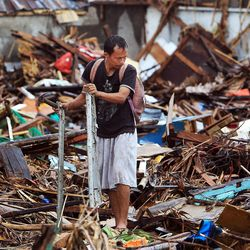 Rollyfer Pepito salvages aluminum from the rubble in Tacloban, Friday, Nov. 22, 2013.
