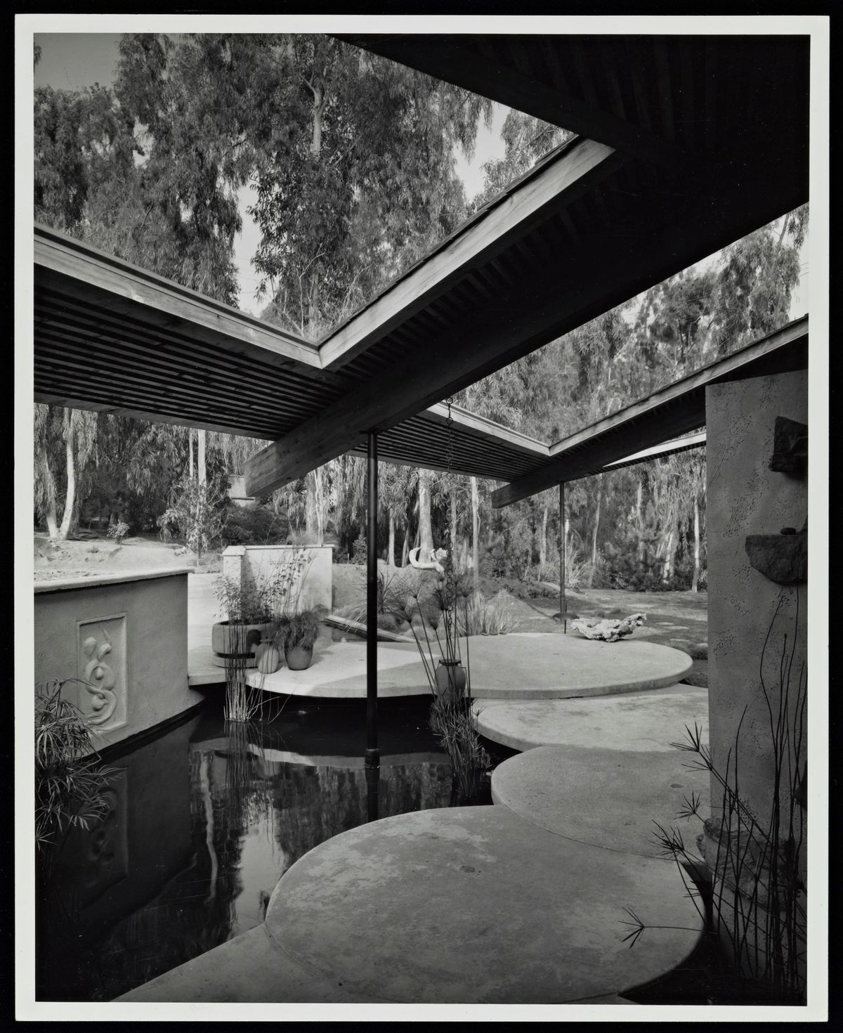 Black and white photograph showing an outdoor area with circular stone path and large overhang.
