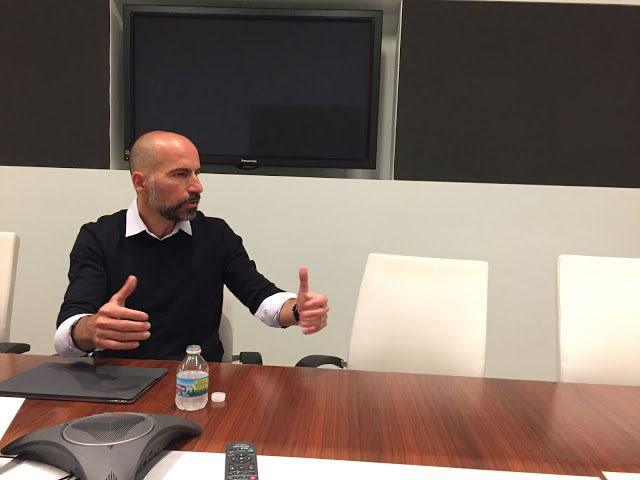 Uber CEO Dara Khosrowshahi talking at a table.