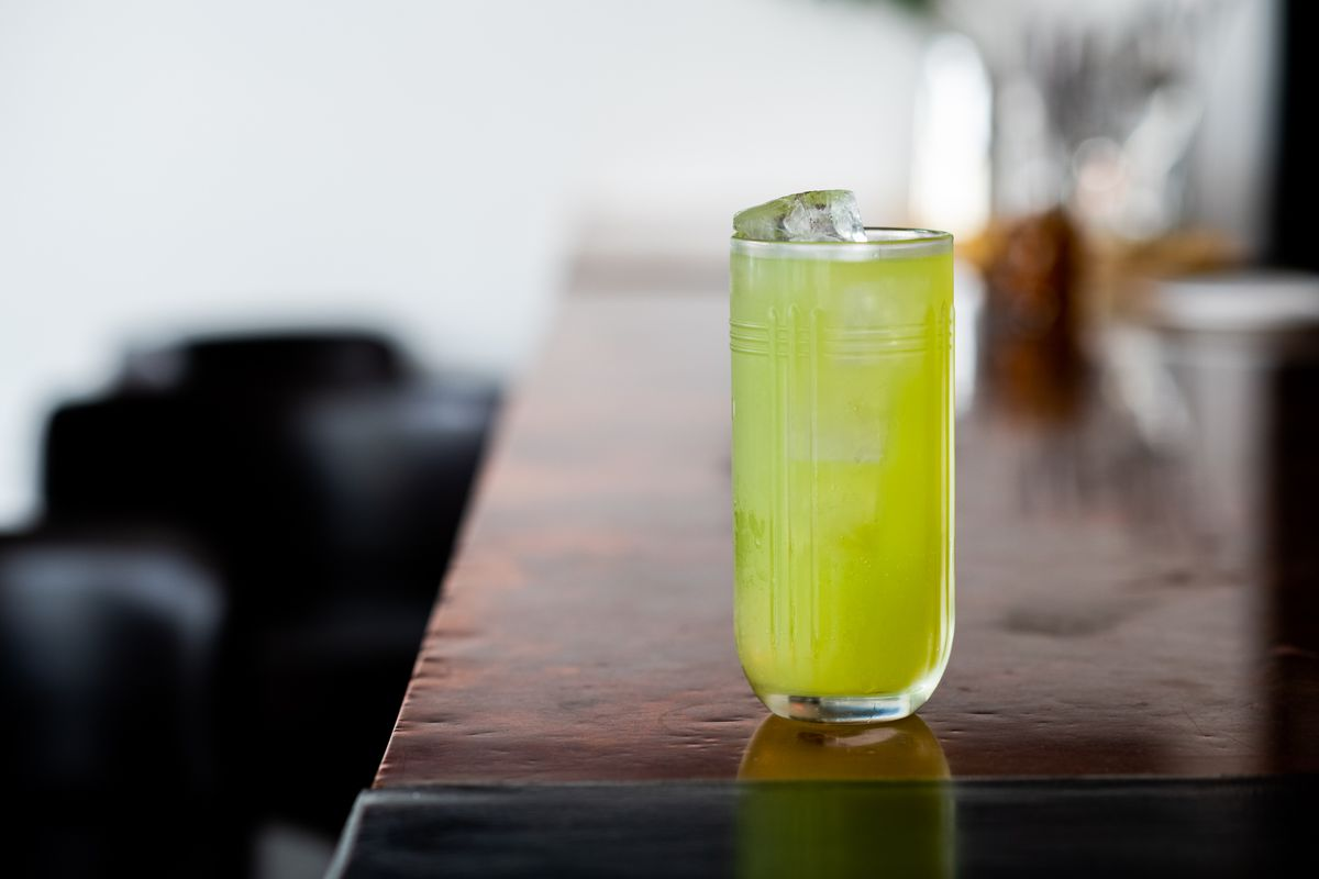 A light green colored drink in a tall glass filled with ice set at the end of the bar.