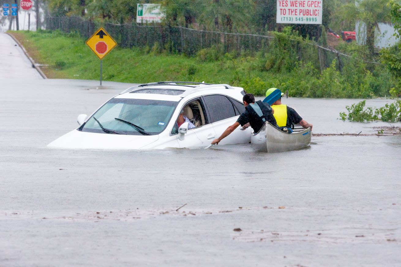 Volunteers in a canoe makes their way to assist a driver that was stalled going through high water during Hurricane Harvey, Monday, August 29, 2017.